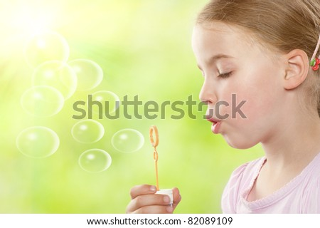 Little girl with soap bubbles in front of green - stock photo