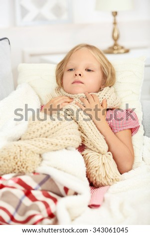 Little girl with sore throat lying on the bed - stock photo