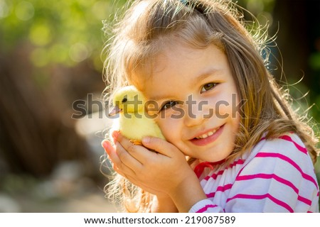 Little girl with spring duckling  - stock photo