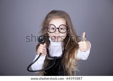 Little girl with  stethoscope show OK. Studio shot. - stock photo