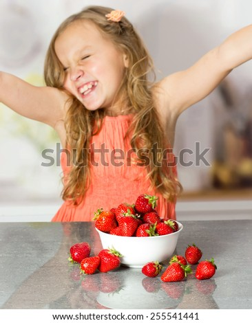 Little girl with strawberry at the table - stock photo