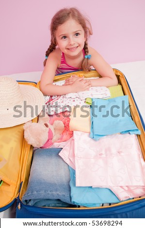 Little girl with suitcase ready for travel