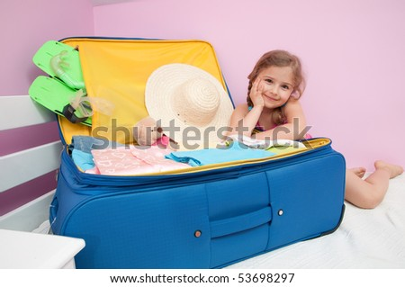 Little girl with suitcase ready for travel - stock photo