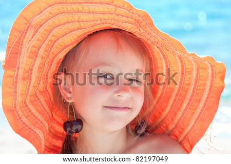 Little girl with sun hat and cherry in ears on beach - stock photo