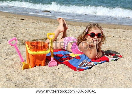 little girl with sunglasses lying on the beach - stock photo