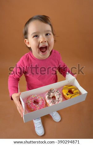 Little girl with sweet different types of donuts - stock photo