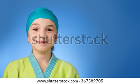Little girl with swimming cap on blue background. Photo has copyspace.