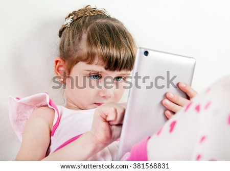 Little Girl with Tablet Computer on White Wall Background - stock photo