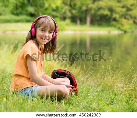 Little girl with tablet pc and headphones listening to music or watching video in summer park at lakeside - stock photo