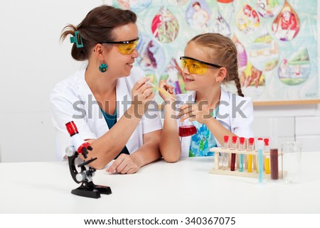Little girl with teacher in elementary science class - doing a simple experiment - stock photo