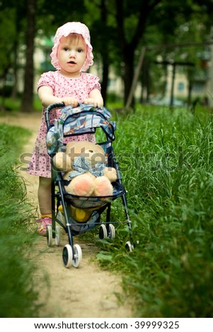 little girl with teddy bear in stroller