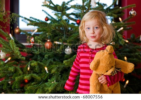 little girl with teddy in front of christmas - stock photo