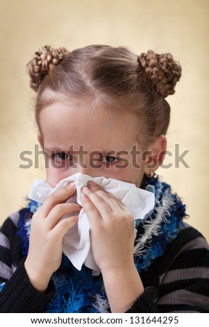 Little girl with the flu having red eyes - blowing nose