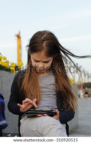 Little girl with the tablet outdoor - stock photo