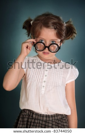 Little girl with thick bottle glasses on green background - stock photo
