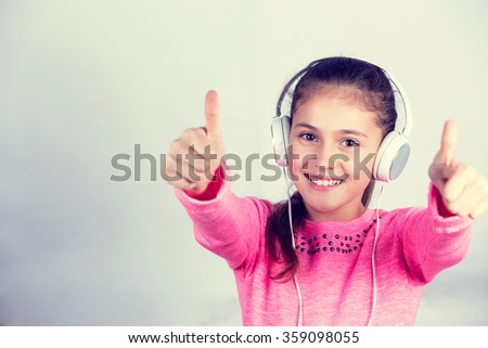 Little girl with thumb up gesture listening to music. - stock photo