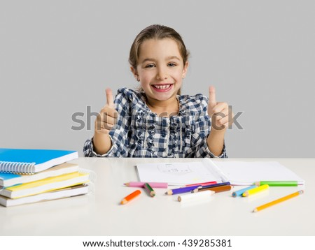 Little girl with thumbs up at school making drawings and painting - stock photo