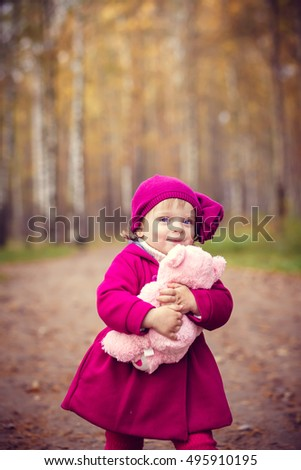 Little girl with toy bear in autumn park