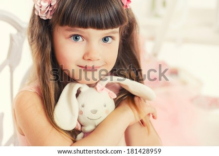 Little girl with toy hare. isolated