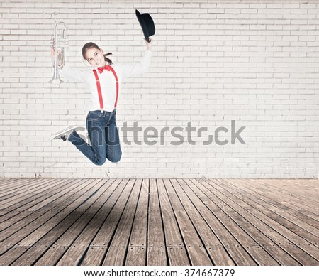 little girl with trumpet jumping on a room with white bricks wall and wood floor