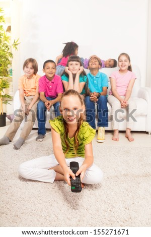 Little girl with TV remote control sitting on the floor in living room with her friends sitting on the coach on background - stock photo
