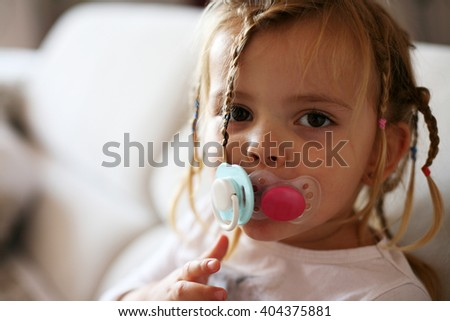 Little girl with two dummy's in mouth.   - stock photo