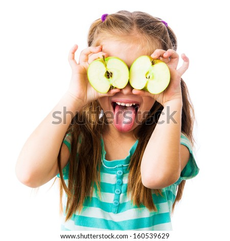 little girl with two halves of an apple near her eyes shows tongue isolated on white background - stock photo