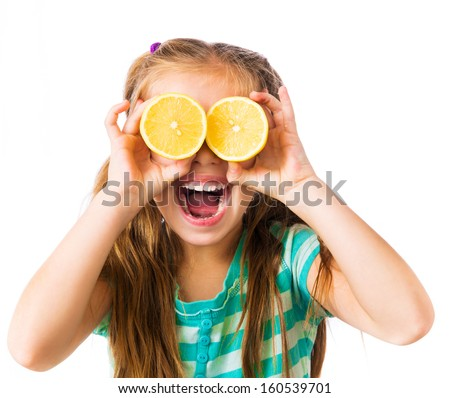 little girl with two halves of lemon as eyes isolated on a white background - stock photo