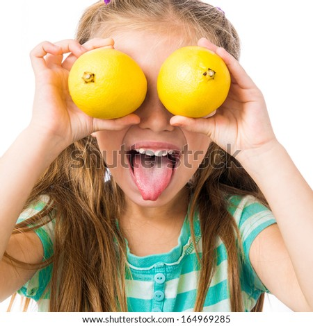 little girl with two lemons shows tongue isolated on white background - stock photo