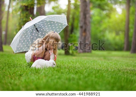 Little girl with umbrella and boots playing with white rabbit in the rain weather. Summer outdoor fun for children