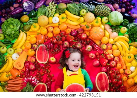 Little girl with variety of fruit and vegetable. Colorful rainbow of raw fresh fruits and vegetables. Child eating healthy snack. Vegetarian nutrition for kids. Vitamins for children. View from above. - stock photo