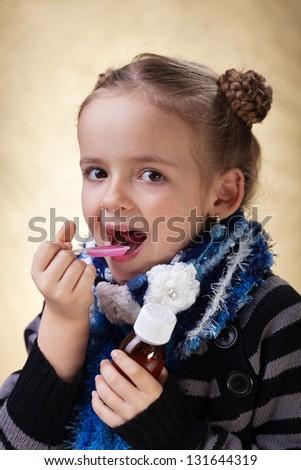 Little girl with warm clothes taking cough medicine syrup - stock photo