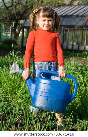 Little girl with watering can is standing on the vegetable garden near onion patch - stock photo