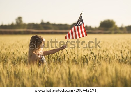 Little girl with wheat field with American flag. - stock photo