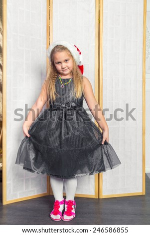 Little girl with white hair in a gray dress red shoes posing standing