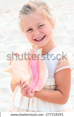 little girl with white hair smiles and holds a sea shell - stock photo