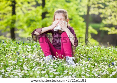 Little girl with with allergy symptom blowing nose - stock photo