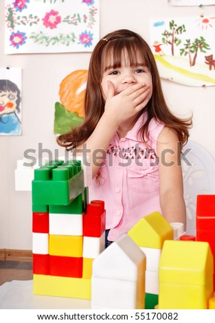 Little girl with wood block in play room.