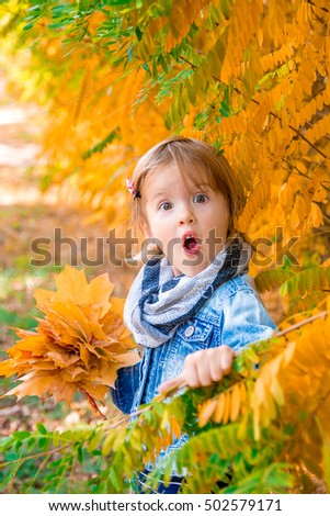 Little girl with yellow autumn golden leaves. Child play outdoors in the park. WOW.