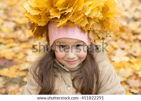 Little girl with yellow autumn wreath on her head on the colorful autumn background