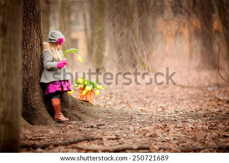 little girl with yellow flowers standing near the tree in the forest at spring time  - stock photo