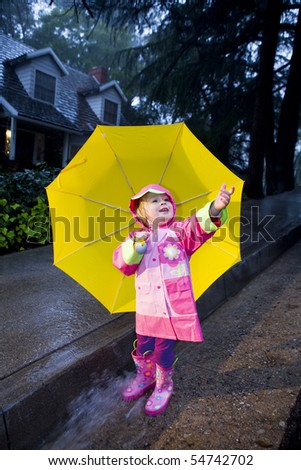 Little girl with yellow umbrella playing in rain wearing pink rain slicker and pink galoshes - stock photo