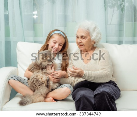 little girl withg randmother playing with cat on sofa
