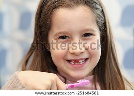little girl without a tooth while brushing teeth in the bathroom - stock photo