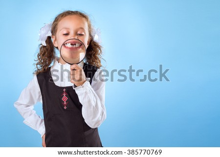 Little Girl Without Teeth Holding A Magnifying Glass Isolated On Blue Background - stock photo