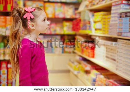 Little girl wonderingly looks on abundance of board games in book department in store - stock photo