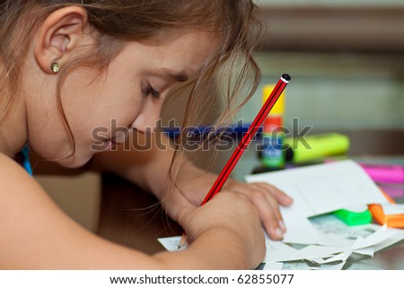 Little girl working on her art project with art materials on the table - stock photo