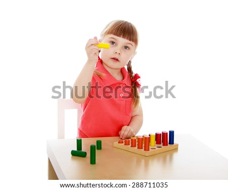 little girl working with the material in the Montessori kindergarten-Isolated on white background - stock photo