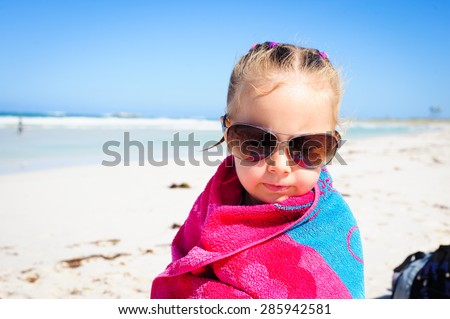 Little girl wrapped in a colorful beach towel and wearing sunglasses sitting at the ocean beach  - stock photo