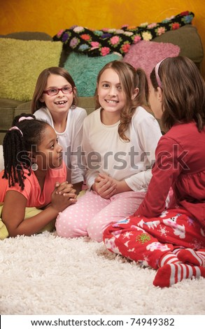 Little girl wrings hands with friends at a sleepover - stock photo